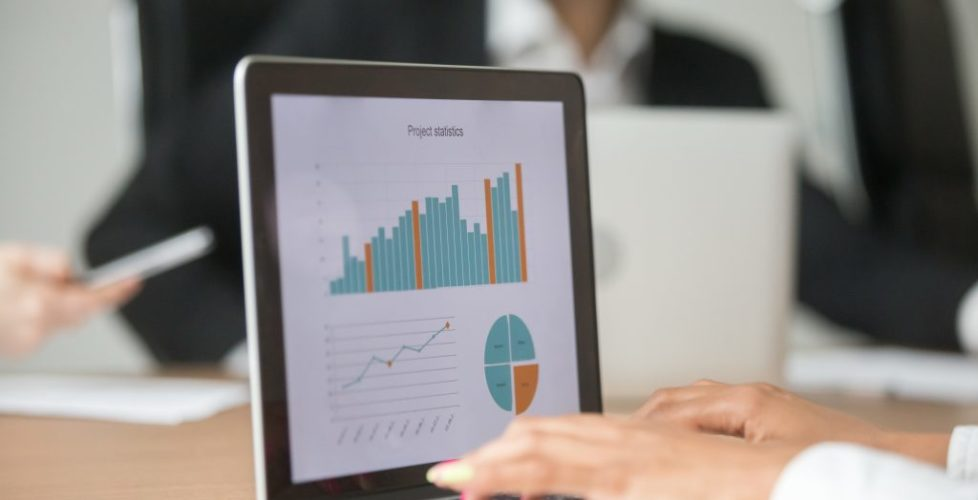 Businesswoman Working With Statistical Report At Team Meeting An