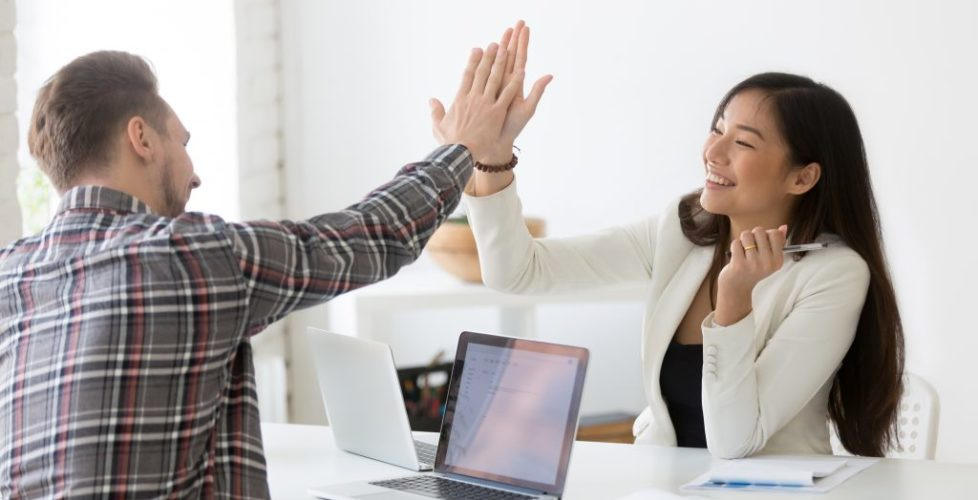 Young Asian And Caucasian Partners Giving High Five At Workplace